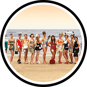 Contestants line the beach in 1920s beach fashion.