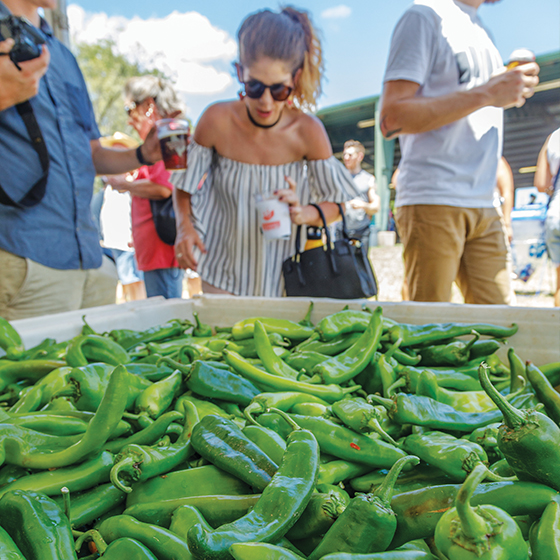 Patrons examine fresh peppers