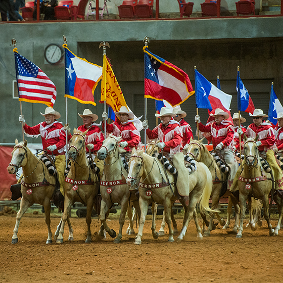 Cowboys riding with American and Texas flags