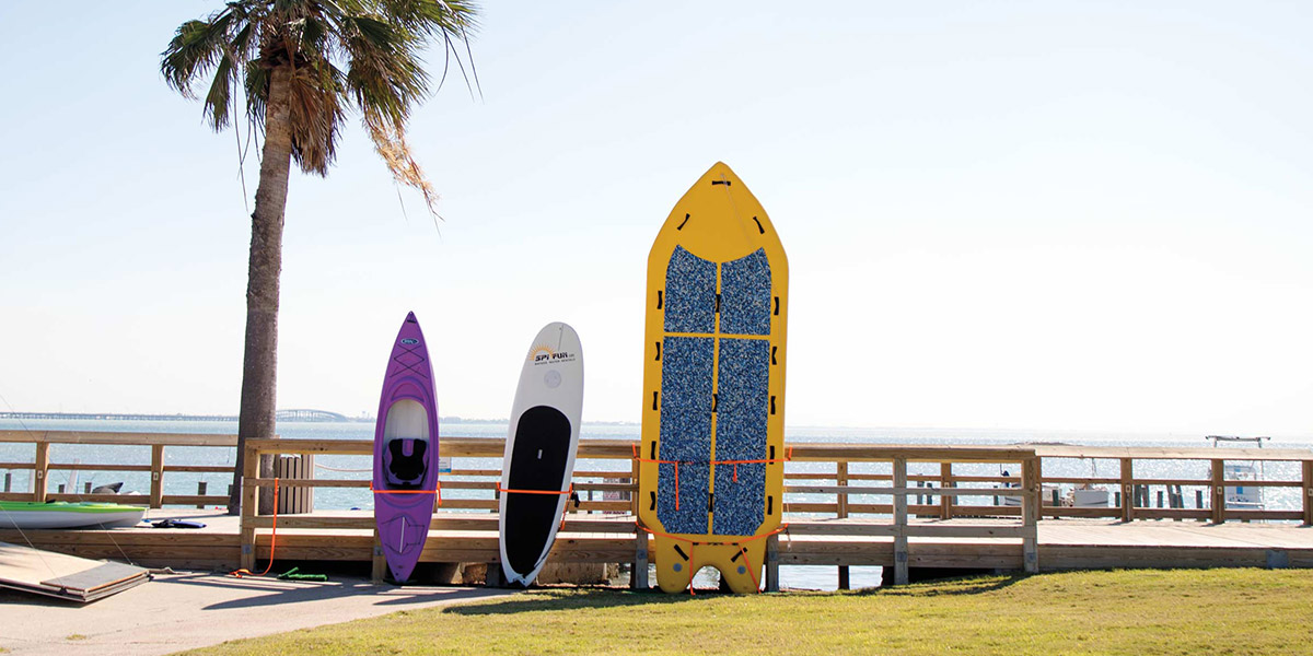 A kayak and 2 paddleboards along the beach on South Padre Island